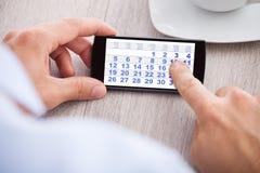 Data de calendário tocante do homem de negócios no telefone celular imagens de stock