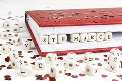 Data de dia do ` s das mulheres escrita em blocos de madeira no caderno vermelho no whi Imagens de Stock