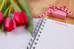 Data del 14 febbraio in taccuino, tulipani freschi e regalo avvolto, giorno di biglietti di S. Valentino Fotografie Stock