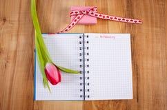 Data del 14 febbraio in taccuino, tulipano fresco e regalo avvolto, giorno di biglietti di S. Valentino Immagini Stock
