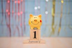 Data di calendario dell'inizio di anno finanziario, il 1° gennaio con il porcellino salvadanaio su fondo blu Orario invernale fotografia stock