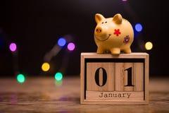 Data di calendario dell'inizio di anno finanziario, il 1° gennaio con il porcellino salvadanaio su fondo scuro immagine stock