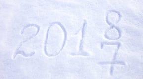 Data 2018 do ano novo escrita no fundo da neve fotos de stock