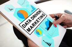 Data driven marketing concept on a paper. Held by a hand stock image