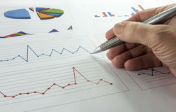 Data graphics analysis. Hand with pen making grafics and analyssis Royalty Free Stock Photography