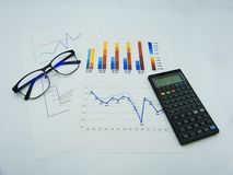 Data graphs and diagrams, glasses and calculator, white background royalty free stock photo
