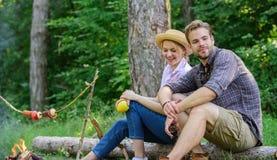 Data idilliaca di picnic Le coppie nel rilassamento di amore si siedono sul ceppo che mangia gli spuntini La famiglia gode del fi fotografia stock