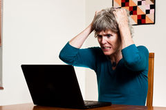 Data Loss: Tearing your hair out. Mature woman tearing her hair out after losing data, frustrated computer user, computer disater black laptop internet problems royalty free stock image