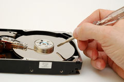 Data manipulation. Opened hard disk and hand holding a screwdriver - conceptual photo: hacker Stock Image