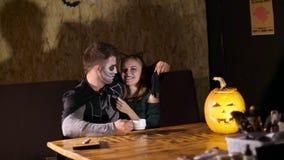 Data nello stile del partito di Halloween, la notte, penombra, nei raggi di luce, il tipo con una ragazza si è vestito in costumi archivi video