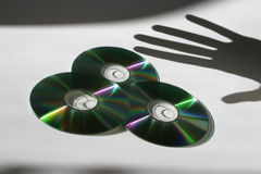 Data Piracy. Three cd`s with a hand ( shadow ) which is stealing information Stock Photo
