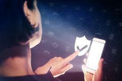 Data privacy, online security, data protection concept. Image of a girl with a smartphone in hands. She presses on the shield icon. Data privacy, online Royalty Free Stock Photos