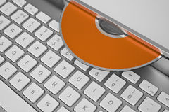Data recovery. An orange CD and a computer keyboard stock image