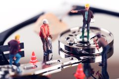 Data recovery concept. construction worker figurines on hard dis. K drive Royalty Free Stock Image
