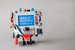 Data recovery concept. IT specialist robotic computer with red pliers, light bulb, warning message on blue display. Gray stock photo