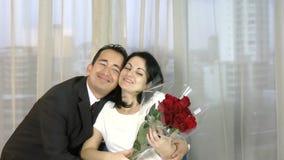 A data romântica dos pares felizes novos, comemorando o homem do dia de são valentim dá rosas vermelhas a sua esposa vídeos de arquivo