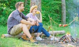 A data rom?ntica dos pares perto da fogueira nos pares da floresta que relaxam senta-se no log que come petiscos Piquenique agrad foto de stock