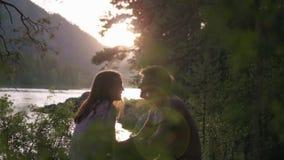 Data romantica degli amanti al tramonto tramite una torrente montano video d archivio