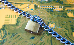 Data Security Encryption Protection Concept with Metallic Padloc. K chained over electronic circuit board background Stock Images