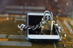 Data Security Encryption Protection Concept with Metallic Padlock chained over smartphone on electronic circuit board background. stock photos