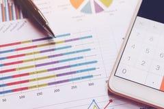 Data som analyserar med räknemaskinen i smart telefon och pennan på diagram royaltyfria bilder