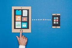 Data sync on cardboard devices. Mobile devices connecting: data sync and file transfer, creative smartphone and tablet made from recycled cardboard Stock Photography