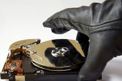 Data Theft. Depiction of the concept of data theft, opened harddisk and gloved hand, stealing information royalty free stock images