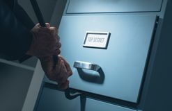 Data theft and security. Burglar opening a drawer in the office at night using a crowbar, he is stealing confidential data and information, data theft and royalty free stock image