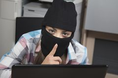 Data thief on computer performs a silent gesture. Woman in the  office situation Stock Photos