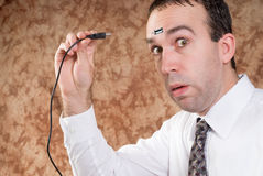 Data Transfer. A man about to plug a USB cable into his forhead to transfer data royalty free stock photography