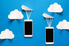 Data transfer concept. Message passing. Two mobile smartphones and paper airplanes. On blue background. Origami. Paper cut stock image
