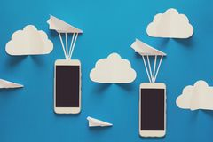 Data transfer concept. Message passing. Two mobile smartphones and paper airplanes. On blue background. Origami. Paper cut. Toned royalty free stock image