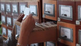 Database concept. human hand opens library card or file catalog box. Close-up student hands in library archive boxes stock footage