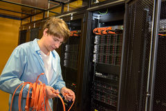 Datacenter engineer rolling up network cables Stock Image