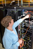 Datacenter technician patching optical cable Royalty Free Stock Image