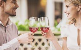 Datación de los pares en restaurante y vino rojo de consumición Imagen de archivo libre de regalías
