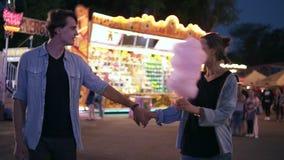 Datación romántica en un parque de atracciones Pares jovenes que caminan por el funfair en la noche La muchacha está sosteniendo  almacen de video