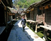 A Chinese man walking down a traditional village street lined by old granaries stock photo