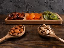 Datas, abricós secados e quivis em um prato Compartmental e porcas em uma colher de madeira em uma tabela de madeira escura foto de stock royalty free