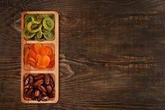 Datas, abricós secados e quivis em um prato Compartmental em uma tabela de madeira escura fotografia de stock royalty free