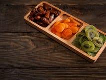 Datas, abricós secados e quivis em um prato Compartmental em uma tabela de madeira escura fotos de stock royalty free