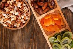 Datas, abricós secados e quivis em um prato e em uma variedade Compartmental das porcas na bacia de madeira em uma tabela de made fotografia de stock