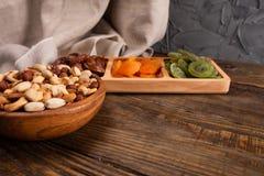 Datas, abricós secados e quivis em um prato e em uma variedade Compartmental das porcas na bacia de madeira em uma tabela de made foto de stock royalty free