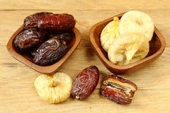 Datas e figos dos frutos na bacia de madeira na tabela Imagem de Stock