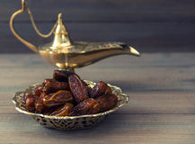 Datas e lâmpada árabe dourada no fundo de madeira imagens de stock