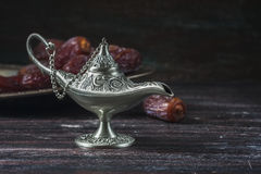 Datas e lâmpada de prata do ` s do aladdin em um fundo de madeira escuro Conceito da ramadã Fotografia de Stock
