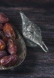 Datas e lâmpada de prata do ` s do aladdin em um fundo de madeira escuro Conceito da ramadã Imagem de Stock