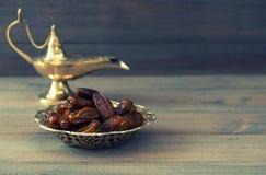 Datas na bacia dourada e na lâmpada árabe O estilo retro tonificou a imagem foto de stock