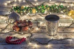 Datas, rosário, e copo da água com escrita de Allah no árabe fotos de stock royalty free