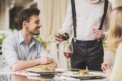 Datation de couples en restaurant et vin rouge potable Images stock